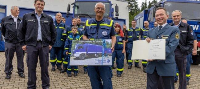 Überraschung geglückt: Viele Kameraden des Ortsverbands Annaberg des Technischen Hilfswerks waren dabei, als Klaus Hauschild (Mitte) aus Anlass seines 80. Geburtstags von Sven Hoppe (rechts), dem Leiter der THW-Regionalstelle Chemnitz, geehrt wurde.