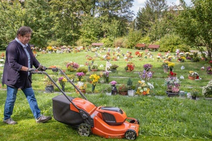 Evelin Noack bei der Rasenmahd. Die regelmäßige Pflege des Friedhofes ist vielen Angehörigen sehr wichtig. Im Hintergrund sind die neuen Wiesenurnengräber zu sehen.