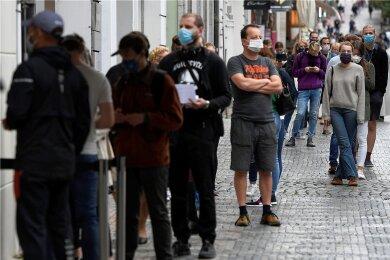 Menschen mit Mundschutz stehen an der Sammelstelle am Wenzelsplatz in Prag Schlange, um sich auf Covid-19 testen zu lassen. In Tschechien breitet sich das Coronavirus weiter rasant aus.