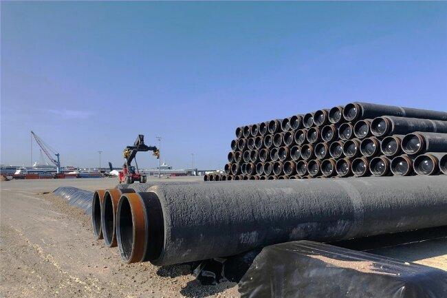 Hunderte Rohre türmen sich auf dem Hafengelände von Sassnitz. Die Stahlleitungen für die letzten Nord-Stream-2-Kilometer haben hier alle schon ihre schweren Betonummantelung erhalten, die allen Meeresströmungen trotzen soll. Wann sie auf das Verlegeschiff geladen werden, steht nun allerdings in den Sternen.