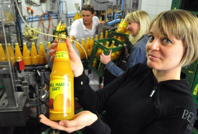 """<p class=""""artikelinhalt"""">Susann Müller (rechts) vom Agenda Verein mit einer der ersten Flaschen Apfel-Mango-Saft, der jetzt in der Firma Heide hergestellt wird. Im Hintergrund Tino Walcha und Daniela Stenzel vom Vertrieb. Eckardt Mildner</p>"""