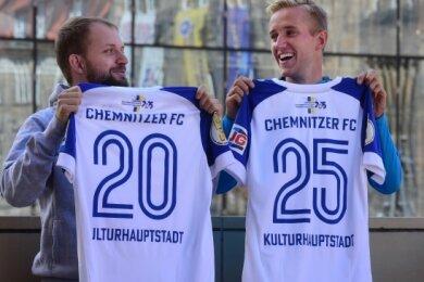 """Niels Vogt vom Fanszene e.V. (links) und CFC-Stürmer Alexander Dartsch haben die Trikots präsentiert, mit denen die Himmelblauen am morgigen Sonntag im DFB-Pokal auflaufen. Anstelle des Schriftzuges """"Kulturhauptstadt"""" werden dann aber wieder die Spielernamen stehen."""