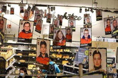 Ein 50 Meter lange Girlande mit den Fotos von Feuerwehrmitgliedern verschiedener Generationen zieht sich durcheinen Einkaufsmarkt in Hohenstein-Ernstthal.