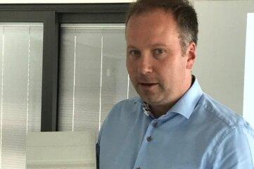 Stadtwerke-Geschäftsführer Lars Lange präsentiert einen digitalen Stromzähler mit Kommunikations-modul.