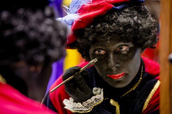 Eine Frau schminkt sich als Zwarte Piet.