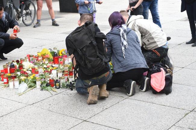 Am Tatort zünden Menschen Kerzen an.