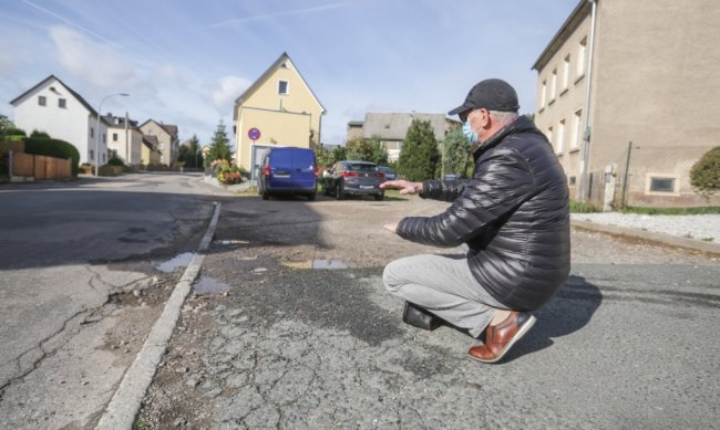 Michael Wuttke zeigt auf den kaputten Fußweg samt Straße. Die Peniger Straße sollte längst gebaut werden. Aber aufgrund von Klagen hat sich der Baubeginn verzögert. Außerdem kritisiert Wuttke die Bedingungen zu seiner Grundstückszufahrt mit Wildwuchs und kaputten Wassereinläufen.