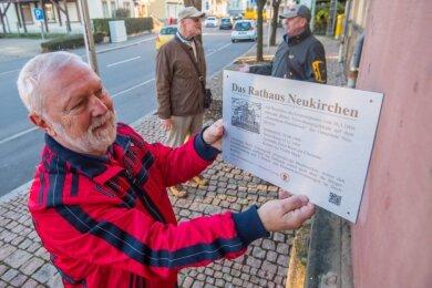 Wolfgang Beyer, Jürgen Beyer und Rolf Schmalfuß vom Heimat- und Geschichtsverein Neukirchen (Foto von links) mit einer Tafel, auf der Angaben zum Rathaus Neukirchen stehen. Sie soll an der Hauswand angebracht werden und über die Historie des Gebäudes informieren.