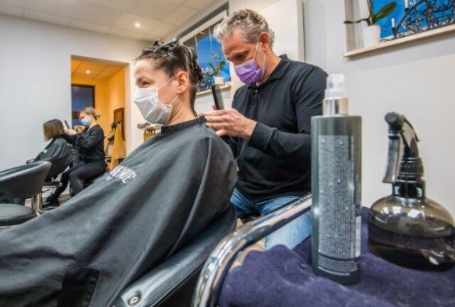 Mike Georgi hat in seinem Friseurladen in Aue am Dienstag vorerst zum letzten Mal Haare frisiert - im Foto zu sehen ist Kundin Dany Winkler. Ab dem heutigen Mittwoch muss das Geschäft geschlossen bleiben.