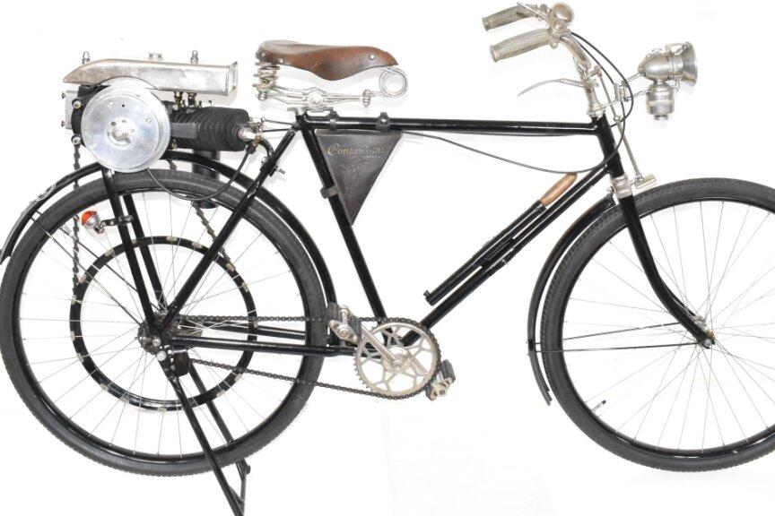 """Mit diesem Fahrrad mit Hilfsmotor feierte DKW am 3. Oktober 1920 den ersten Sieg bei einem Motorradrennen auf deutschem Boden. Als Antrieb diente ein Zweitakter mit 118 Kubik und 1 PS, Höchstgeschwindigkeit über 60 km/h. Der Werbeslogan damals: """"Das kleine Wunder fährt Berge rauf wie andere runter""""."""