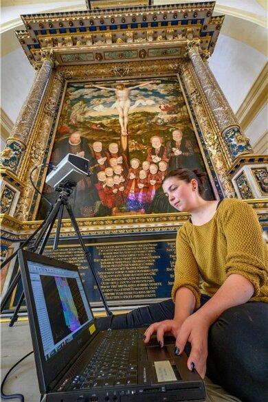 Hightech trifft Cranach: In der Schlosskirche zu Augustusburg scannt Anne Karl, wissenschaftliche Mitarbeiterin der Uni Bamberg, das Gemälde mit einem 3D-Scanner, mit dem auch kleinste Risse sichtbar werden.