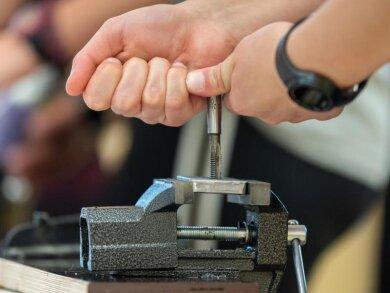 Die Hände einer Schülerin sind zu sehen, während sie an einem Schraubstock ein Gewinde in ein Metallteil bohrt.