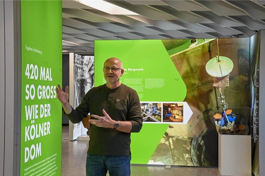 """Frank Wolf, Sprecher der Wismut, erklärt die Ausstellung mit dem Titel """"Für die Menschen. Für die Umwelt. 30 Jahre Wismut GmbH""""."""