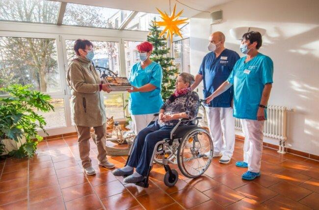 Birgit Fischer (links) bedankt sich mit einem Stollen bei den Pflegekräften Claudia Wendler, Gunther Adler und Iris Reiprich, die auf der Station arbeiten, auf der Birgit Fischers Mutter Helga Zürch betreut wird.