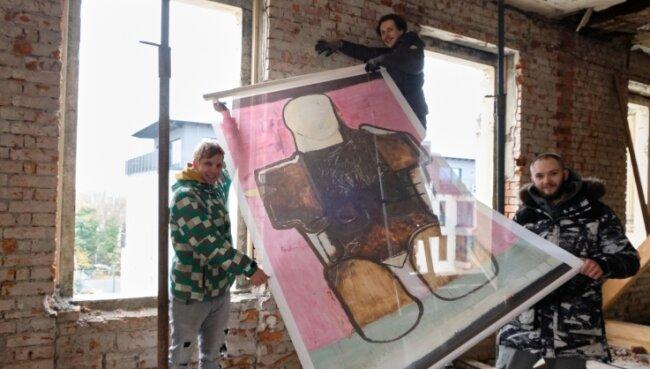 Kunst auf winddurchlässiger Gaze. Severin Zähringer, Robert Seidel und Gregor Steps (von links) beim Ausstaffieren der Galerie.