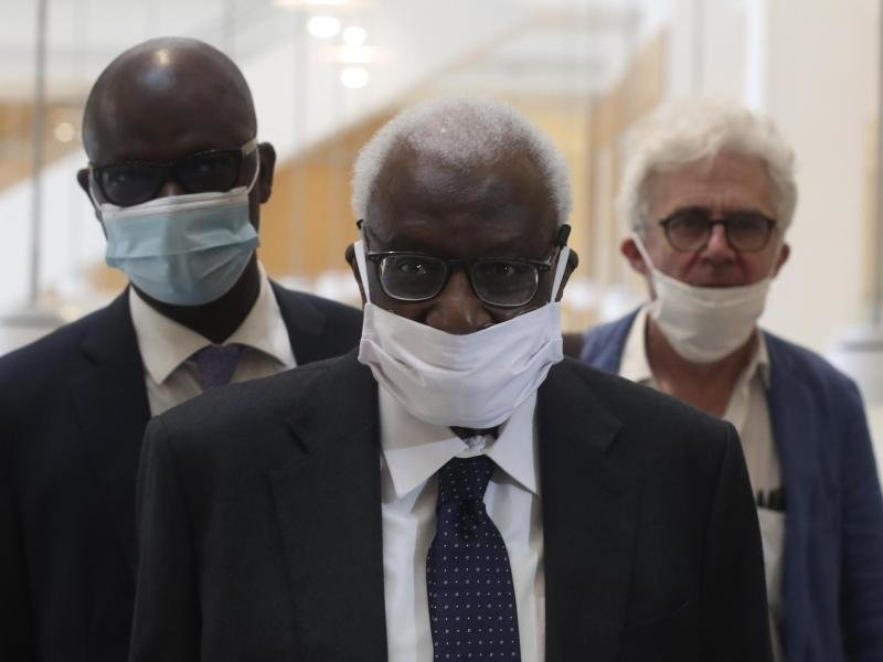 Den Corona-Regeln entsprechend mit einer Maske kommt Lamine Diack (M) mit seinem Anwalt William Bourdon (r) ins Pariser Gericht.
