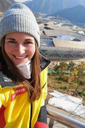 Selfie mit Olympiabahn: Stolze 1900 Meter lang ist die Eisschlange im Jundu-Shan-Gebirge, sie hat 16 Kurven und eine Höhendifferenz von 127 Metern zwischen Herrenstart und Ziel. Für die Damen sind es zwei Kurven und jeweils ein paar Meter weniger. Julia Taubitz hat sich sofort in die Anlage verliebt.