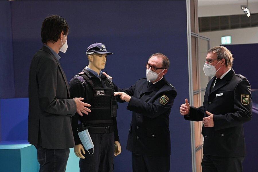 Jens Beutmann (links) nimmt die Leihgabe für die Ausstellung von den Polizisten Wolfgang Schütze und Lutz Wodarsch (rechts) entgegen.