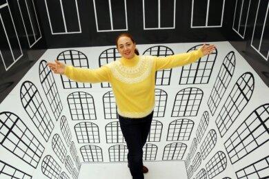 """Patrizia Meyn, Geschäftsführerin der sehenswerten Drei, steht in einer 3D-Illusion in der Sonderausstellung """"Ausgetrickst"""" im Schloss Augustusburg. Die interaktive Schau ist bis 2022 verlängert."""