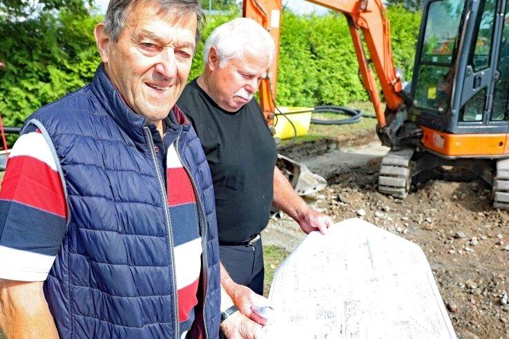Projektant Volkmar Dittrich (l.) und Vereinsvorsitzender Heinz John mit den Plänen des Vereinshauses. Hinter den beiden Männern wird bereits an der Umsetzung des Vorhabens gearbeitet.