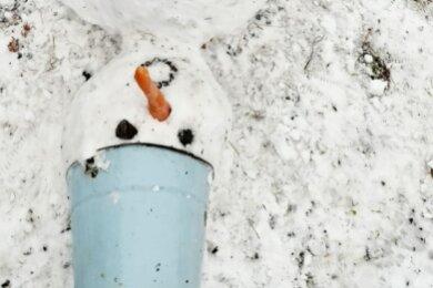 """Bloß gut, dass dieser Schneemann in Weißenborn einen """"Sturzhelm"""" trägt: Es hat ihn einfach umgehauen."""