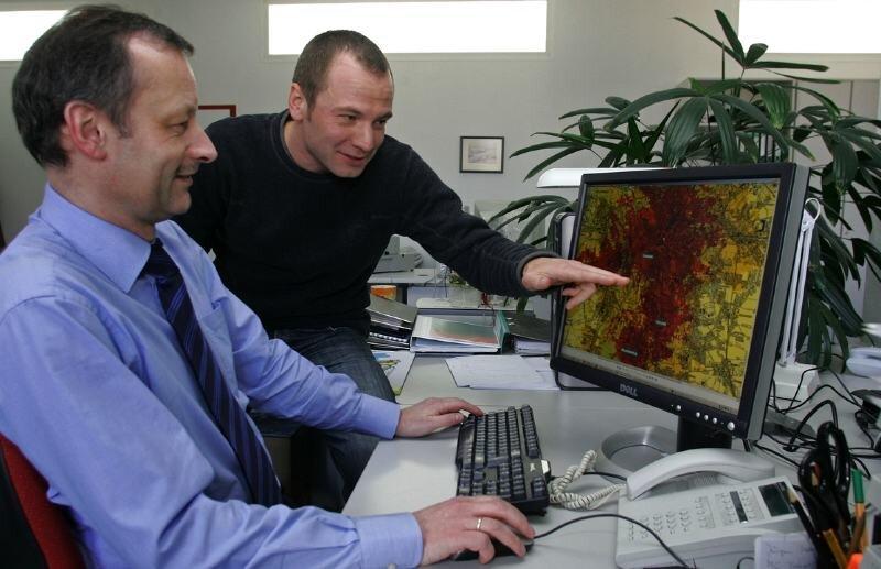 """<p class=""""artikelinhalt"""">Lutz Illing (hinten) und Uwe Graich von der Firma Mugler erklären an einer Karte die Verbreitung des neuen digitalen Rundfunksystems im Leipziger Raum. </p>"""
