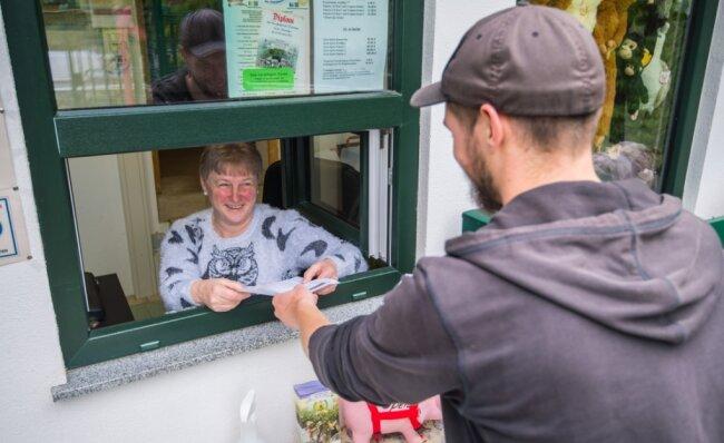 Im Zoo der Minis in Aue erfolgt der Einlass sehr flexibel. Hier nimmt Kassiererin Petra Hörenberg die ausgedruckte Reservierungs-Mail eines Besuchers entgegen. Sie dient der Kontaktnachverfolgung. Wer daheim keinen Drucker hat, kann das Formular auch an der Kasse ausfüllen.