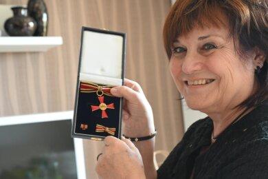 Kerstin Stopp mit ihrem Bundesverdienstkreuz. Es liegt nun in einer Vitrine in ihrem Wohnzimmer. Viel Zeit, es anzusehen, hat sie nicht.