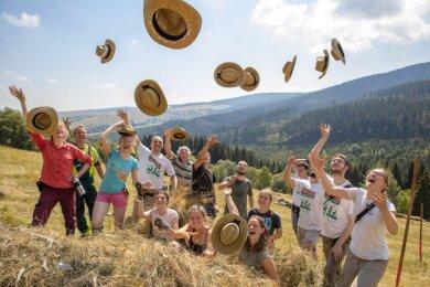 Ihren Humor haben die Teilnehmer des diesjährigen Bergwiesencamps in Oberwiesenthals trotz schweißtreibender Arbeit noch nicht verloren. Zumal die Sommerhüte als kleines Dankeschön für zwei Wochen ehrenamtlichen Einsatz am Freitagvormittag gerade recht kamen.
