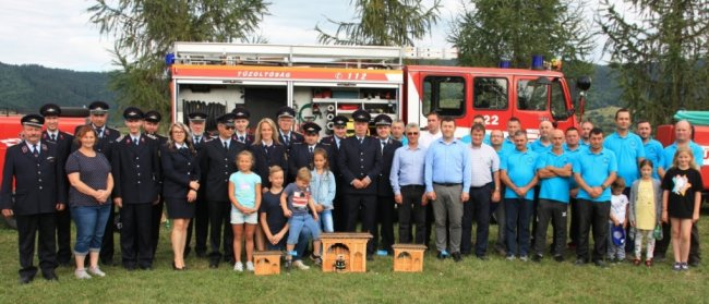 Feuerwehrleute aus Milkau (l.) sowie ihre Kollegen aus Rumänien (r.) haben die Übergabe des Fahrzeugs mit einem Dorffest gefeiert. Als Geschenk für die Sachsen gab es unter anderem typische Eingangstore im Miniaturformat.