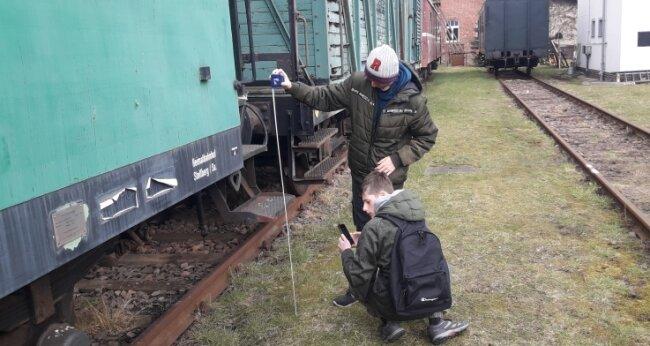 Sebastian Jung und Tim Heidel von den Lugauer Eisenbahnfreunden waren extra in Hilbersdorf, um auszumessen, ob der Waggon für ihre Zwecke taugt.