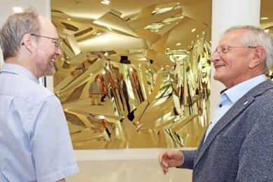 """Professor Bernd Meyer (rechts), Technischer Direktor des ZeHS, demonstrierte auf heitere Weise Professor Michael Schlömann, der als Besuchergekommen war, die Wirkungsweise der Spiegel im Kunstwerk """"Solaris"""" im Foyer."""