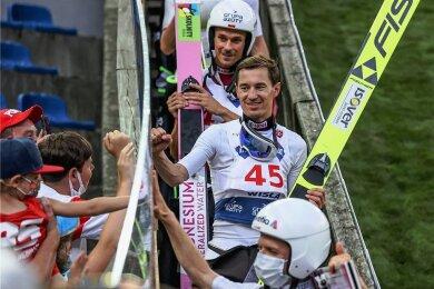So war es beim Sommer-Grand-Prix in Wisla: Die 999 zugelassenen Fans standen hinter einer Plexiglasscheibe im Auslauf. Die Olympiasieger Simon Ammann (mit Maske vorn) und Kamil Stoch (Nummer 45) grüßen dahinter.