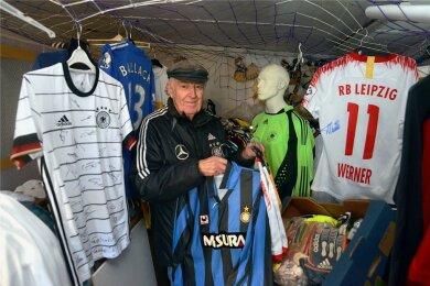 Wilfried Metzler in seiner Garage inmitten seiner Sammlerstücke. Links hängt das Trikot der deutschen Fußballnationalelf, das er zum Geburtstaggeschenkt bekommen hat.
