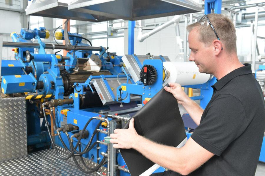 Technikumsleiter Martin Schneider zeigt am Schmelzwalzenkalander eine Probe Kunstleder.