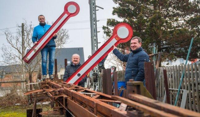 Der Brünloser Jens Hanisch (links) will das alte Eisenbahnsignal vom Zwönitzer Bahnhof (liegend) restaurieren lassen. Die Zwönitzer Stadträte Reinhard Troll (Mitte) und Tim Schneider haben sich für die Realisierung des Vorhabens eingesetzt. Die neuen Flügel für das Signal gibt es schon.