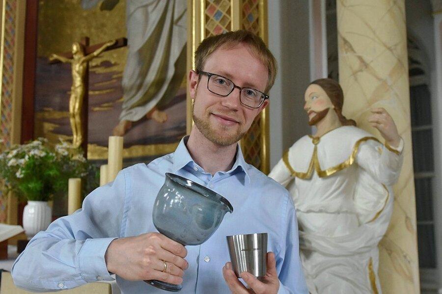 Pfarrer Philipp-Imanuel Albert mit einem der Abendmahlbecher und dem Gießkelch.