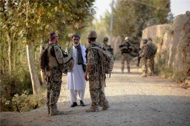 Ein Bundeswehrsoldat (links) und ein afghanischer Dolmetscher (rechts) sprechen nahe Kundus mit einem Einheimischen. Nach dem Abzug der Bundeswehr sind viele einstige Helfer in Lebensgefahr.