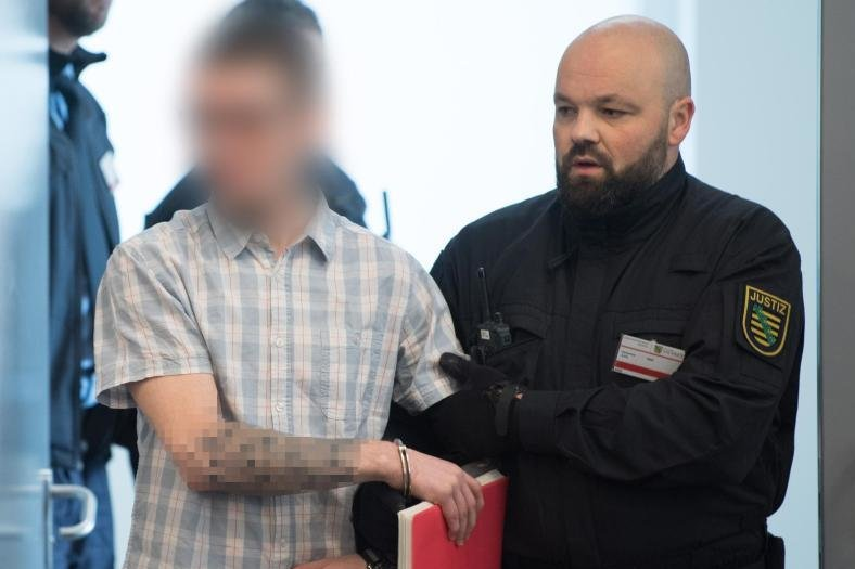Ein Angeklagter wird im Oberlandesgericht Dresden zu Prozessbeginn in den Verhandlungssaal geführt.