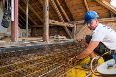 Ein Mitarbeiter der Rochlitzer Baufirma HTB flechtet im Dachgeschoss Eisen, damit im westlichen Treppenhaus eine Decke aus Beton gegossen werden kann.