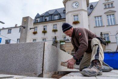 Steinmetz Dieter Anders baute jetzt die aufgearbeiteten Granitplatten der Brunneneinfassung ein. Damit der Marktbrunnen nächstes Jahr wieder sprudelt, muss noch das Wasserbassin abgedichtet werden.Foto: David Rötzschke