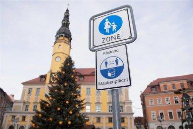 Der Lockdown mit geschlossenen Geschäften und Restaurants gehört vorerst zu unser aller Leben: Ein Hinweisschild weist auf Maskenpflicht und Abstandsregeln vor dem Rathaus in Bautzen hin.