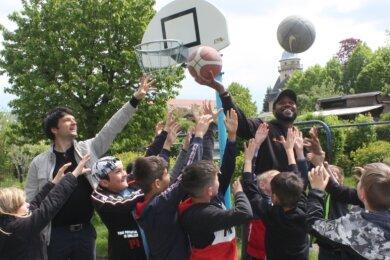Rotarier Frank Joachim Seidel (hinten links) hat Basketballer Virgil Matthews eingeladen, um mit Kindern zu spielen.