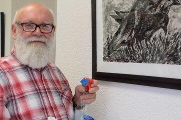Um seine Bilder im besten Licht zu zeigen, poliert Klaus Neubert nach dem Hängen das Glas der Bilderrahmen. Ab Montag sind die Arbeiten des Oelsnitzer Malers im Hohndorfer Rathaus zu sehen.