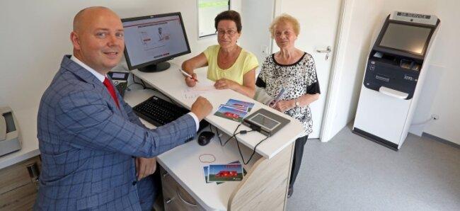 Unternehmenssprecher Sven Mücklich zeigt Gabriele Martin (links) und Lore Landgraf das neue Sparkassenmobil.