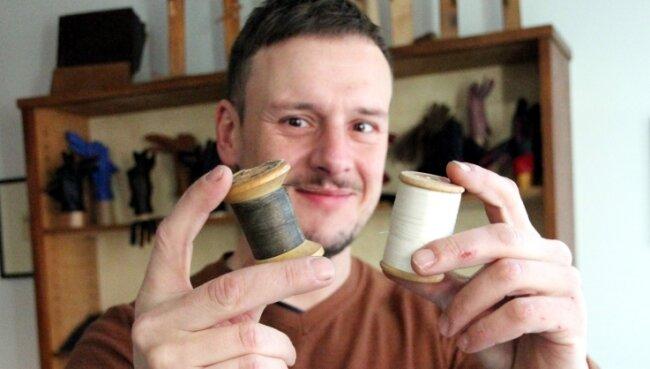Mit solchen Holzgarnrollen arbeitet Nils Bergauer noch heute in seiner Handschuh-Werkstatt. Sie wurden auch beim Bau der Pyramide verwendet, die nun das Schaufenster ziert.