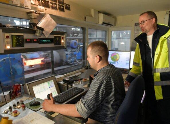 Christopher Naumann (l.) und Werkleiter Uwe Heise beobachten in der Meßwarte der Schmiedeanlage das Schmieden von Radsatzwellen.