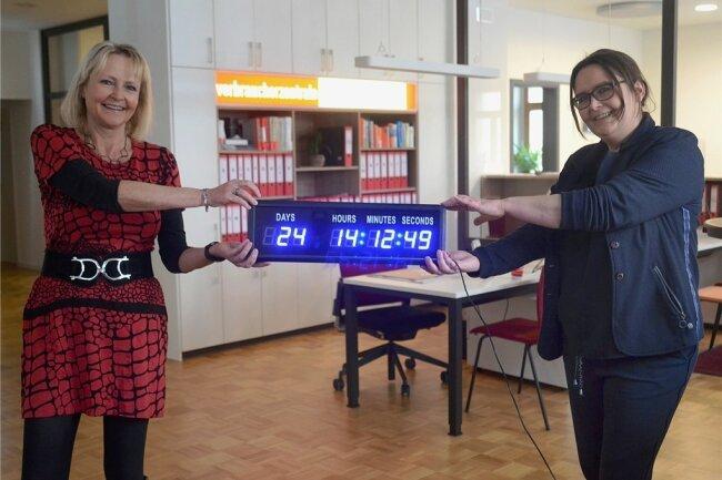 Heike Teubner (l.) und Nicole Leistner präsentieren die neue Countdown-Uhr in der Beratungsstelle Auerbach: Am Freitag blieben noch 24 Tage für die Anmeldung im Klageregister.