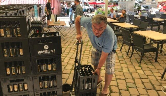 Siegfried Eichler lädt sich zwei Kisten Craft-Beer auf seinen Handkarren. Damit spendete er zugleich 20 Euro für den CFC.