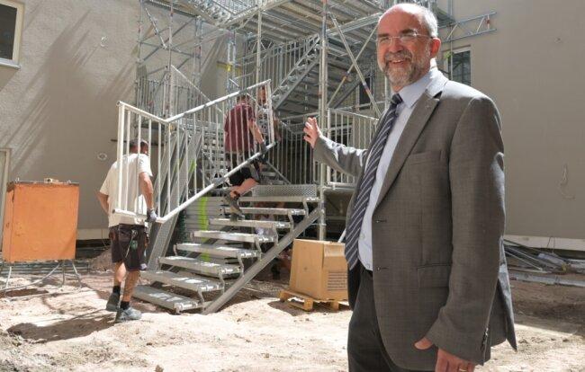 WBG-Geschäftsführer Peter Stimpel vor dem Neubau an der Königlich-Sächsischen Zeichen- und Klöppelschule. Dort musste zunächst eine provisorische Treppenanlage angebaut werden.